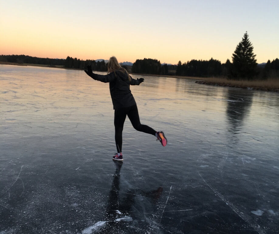 Ich schlittere in Sportklamotten über einen zugefrorenen See.