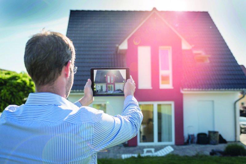 Mann fotografiert Haus mit Tablet