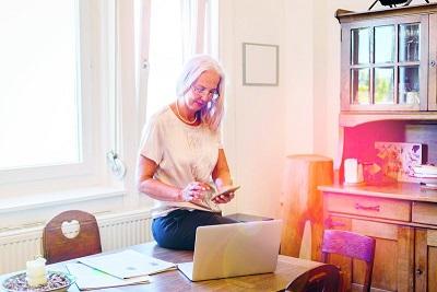 Ältere Frau mit einem Smartphone und Laptop