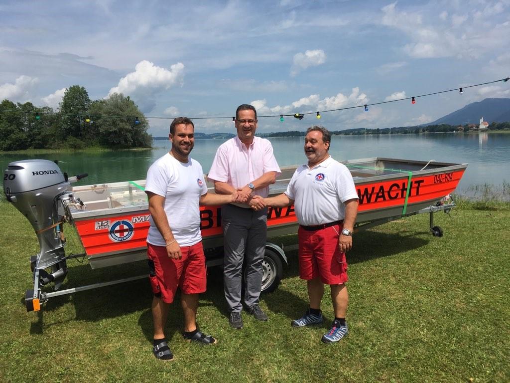 Max Achatz (Technischer Leiter Wasserwacht Füssen), Rochus Nickl (stv. Vorstandsmitglied Sparkasse Allgäu) und Rudolf Achatz (1. Vorsitzender Wasserwacht Füssen) vor dem Rettungsboot.