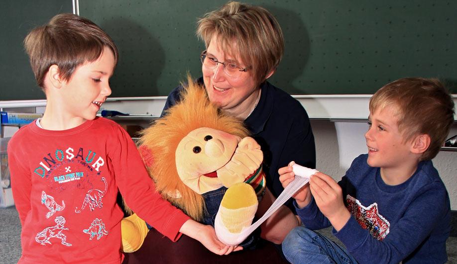 """Puppe Solfi wird beim Erste-Hife-Kurs """"Trau dich"""" von den Kindergartenkindern verbunden"""