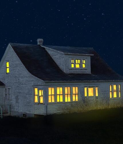 Beleuchtetes Haus bei Nacht.